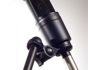 A black microphone on a white background sitting on a stand.