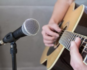 Close up of the hand of a guitarist strumming an acoustic wooden guitar into a microphone at a concert or performance
